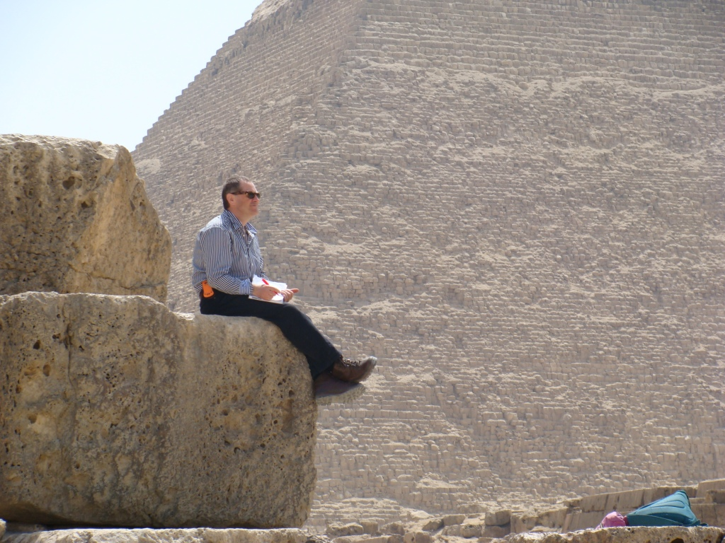 Norman is in deep thought as he writes his diary, sitting on the corner of the Great Pyramid with Khafre's pyramid in the background.
