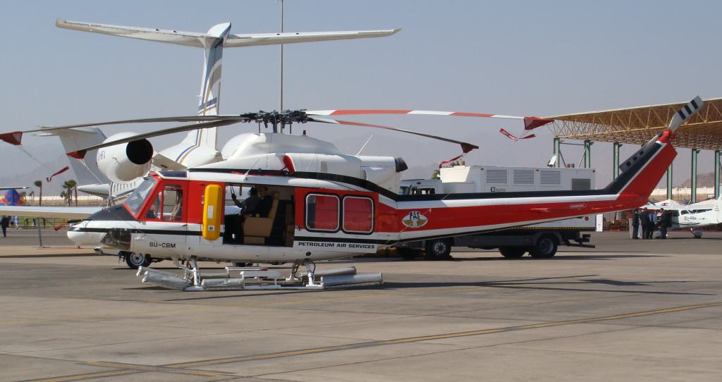 Sometimes, the lack of space on a tail or no tail means that registration has to be applied somewhere else. Here the Egyptian registration, SU-CBM is applied just under the cabin window of this Bell 412