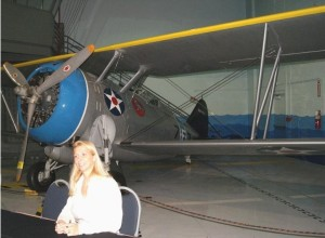 "Stacie Rine chats with attendees in Fantasy of Flight's ""Carrier Deck"" room. The facility's Grumman F3F, sporting U.S. Navy livery, sits in the background. (Photo by John Stemple.)"